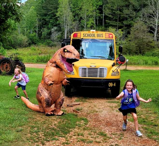 Man in a dinosaur costume chasing a little girl at a bus stop